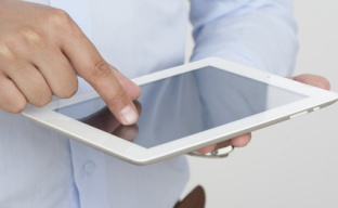 A computer ipad tablet with a hand touching a touchscreen